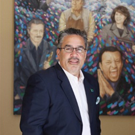 Peter Guzman with a painting behind him