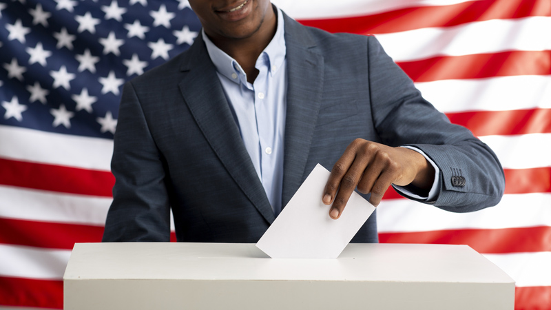 A voter adding his vote to the ballot with an American flag behind him